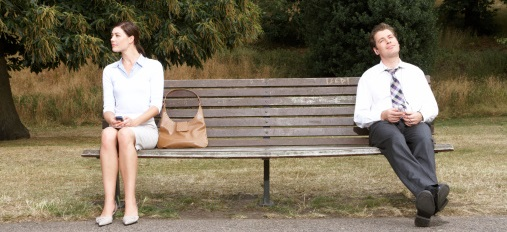 Businesswoman and businessman sitting on park bench